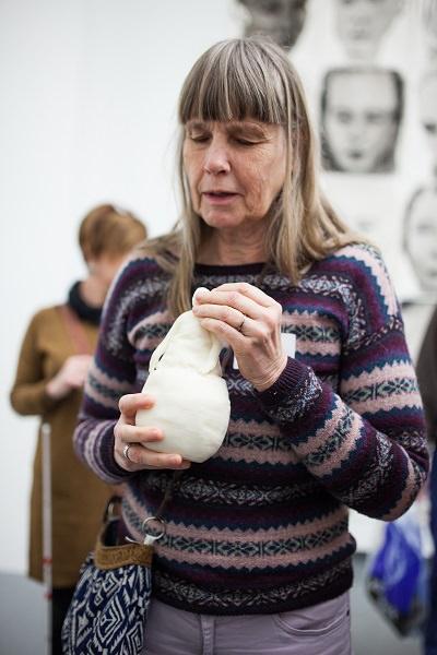 Een blinde bezoeker met een replica van een beeld van Juan Munoz in de hand.