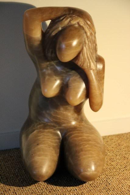 Knielend vrouwenfiguur met de rechterhand op het hoofd en de linker onder het haar aan de linkerkant van het hoofd, materiaal is bruine albast.