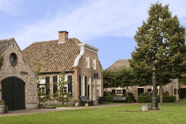 Dorpsplein van het Boerenbondsmuseum met oude ambachtsgebouwen zoals een wevershuisje, klompenmakerij en smederij.