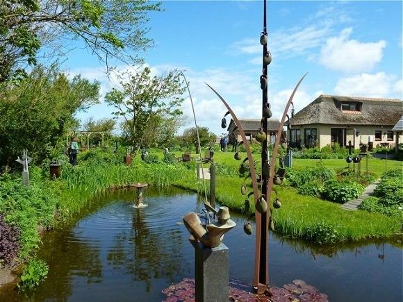 Op de foto is een deel van Beeldentuin De Booghgaard te zien, met de vijver waarin ook beelden geplaatst zijn.