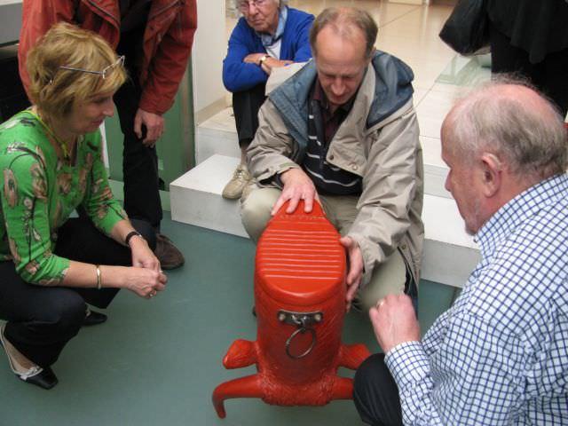 George Kabel bekijkt een zitmeubel in de vorm van een toiletpot