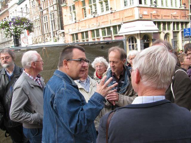 Op het drukke marktplein verhaalt de gids over de geschiedenis van Gent