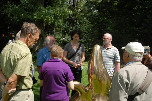 Groep luistert aandachtig naar uitleg over beeld van Hans Arp
