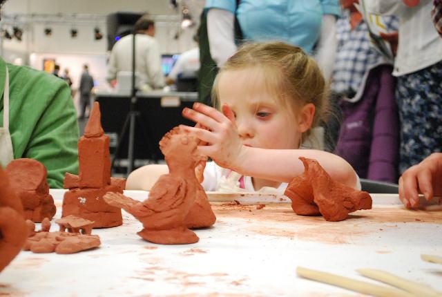 Zeer geconcentreerd werkt deze jonge bezoekster mee aan de totstandkoming van een maquette tijdens de Workshop boetseren