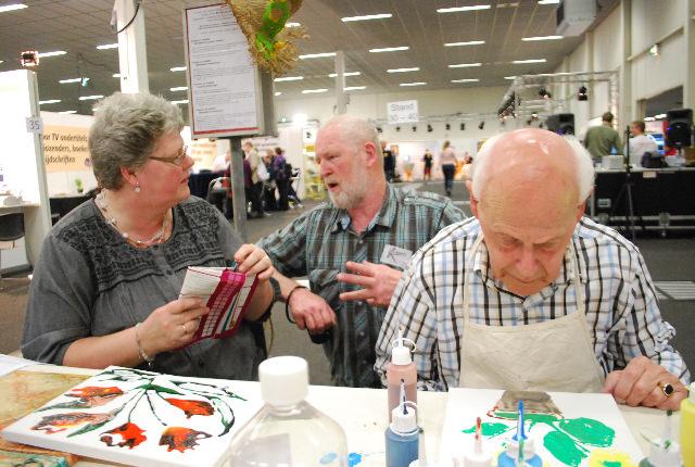 Adri Hopman legt een bezoeker het e.e.a. uit over Stichting KUBES