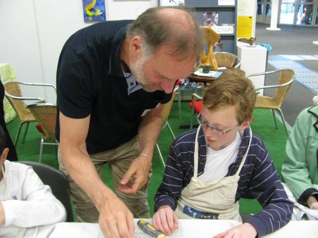 KUBES vrijwilliger Peter Hiep geeft uitleg over speksteen bewerken