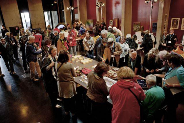 Bezoekers kunnen aan een lange tafel diverse kunstobjecten bekijken en betasten
