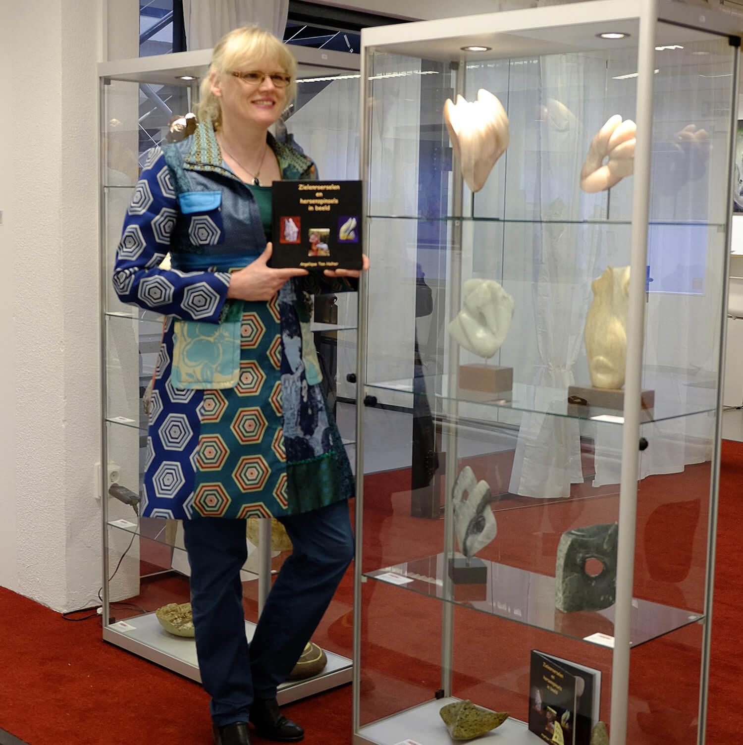 Angelique naast een vitrinekast met haar beelden