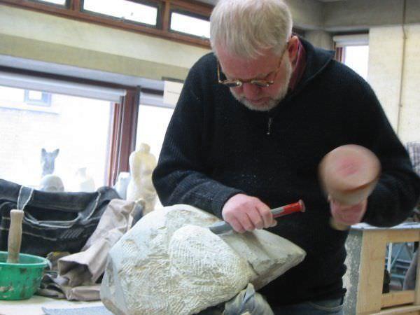 Leendert Wijtman aan het beeldhouwen in steen